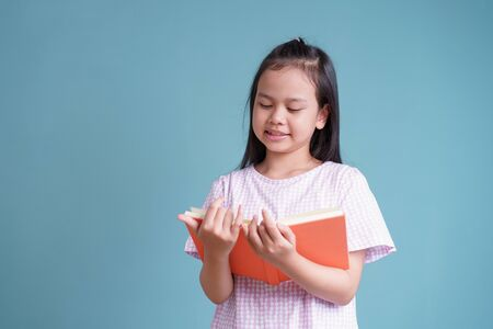 happy Asian little girl standing reading the book on blue background isolated Stock fotó