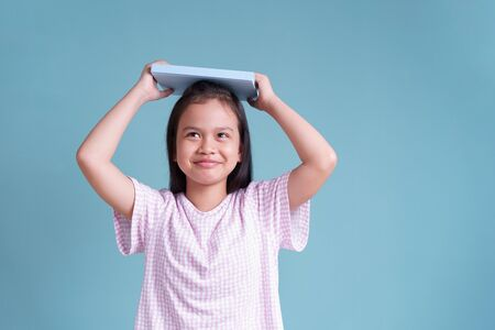 happy Asian little girl standing put the book on head on blue background isolated