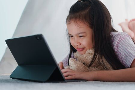 Asian little girl using tablet in a tent at home night, Asia child typing work on digital computer