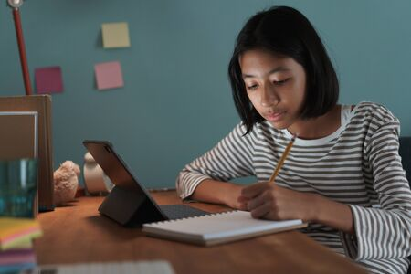 Homeschooling Asian girl doing homework And study online with tablet at a desk at night.