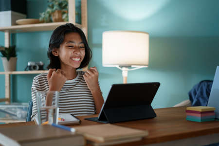Education. happy Asian little girl successfully is studying online via the internet on tablet digital while sitting on desk at home night. Concept of online learning at home