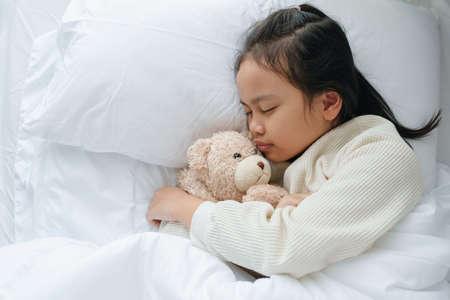 Asian little girl sleeping and hug teddy bear in the bedroom Stock fotó