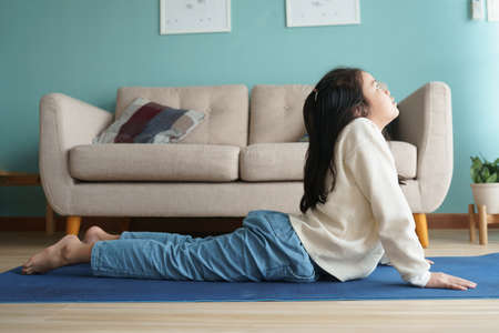 Asian little girl practicing yoga cobra pose on yoga mat in the living at home, Concept of relaxation and meditation Stock fotó