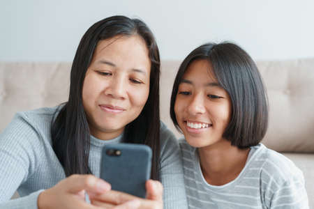 Family Asian mother and daughter watching entertainment online on smartphone together at home. Happy girl and mum while sitting in the living room togetherness. Close-up on face child and mom Stock fotó