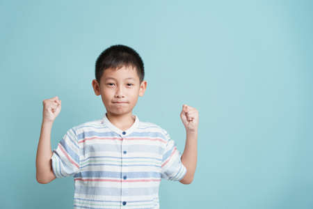 happy Asian little boy standing on blue background isolated, Portrait of cute man success happiness and smile
