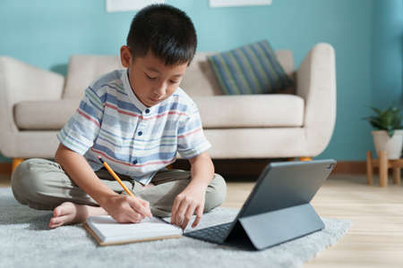 Education. Asian boy learning and doing homework with the online teacher on tablet digital at home