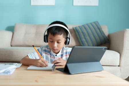 Education. Asian boy learning and doing homework with the online teacher on tablet digital with headphone at home