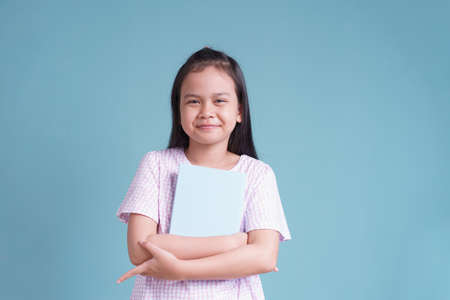 happy Asian little girl standing holding the book  on blue background isolated Stock fotó