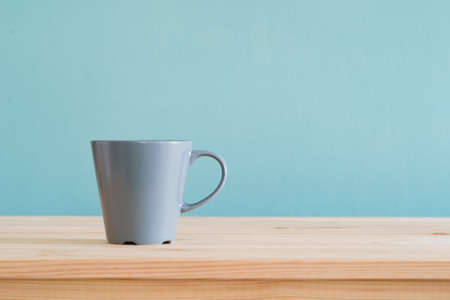Coffee mugs place on brown wood desk and blue wallpaper textured background with copy space