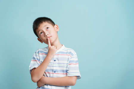 Asian little boy standing thinking on blue background isolated, Asia man look up and copy space