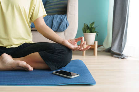 Hand of woman in lotus pose while sitting at mat yoga, Asian women practice yoga. With an online Trainer on mobile phone at home. Concept of relaxation and meditation
