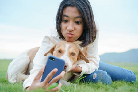 happy Asian girl Take a photo a dog and playing with smartphone On the green lawn together close-up at morning