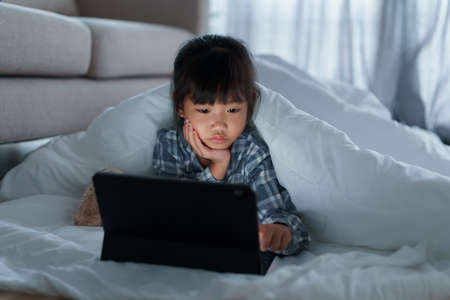 Asian Little girl using tablet digital under a blanket in the bedroom at night