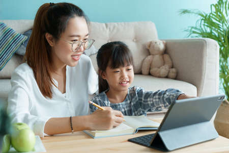 Homeschooling. Asian family with daughter doing homework by using tablet with mother help. Asia mom and child learning online with laptop computer together in the living room at home Stock fotó