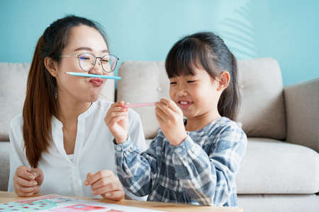 happy Asian family that has a mother and daughter sitting playing enjoying and activity together at home and sunlight morning Stock fotó