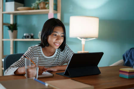 Homeschooling Asian girl doing homework and study online with tutor on tablet digital at home at night