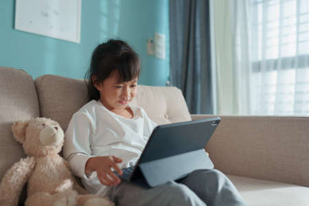 Happy Asian little girl using tablet digital while sitting on the sofa with teddy bear at home in the morning