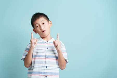 Asian little boy standing thinking on blue background isolated, Portrait of cute man points up