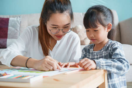 Asian family with mother and daughter doing together activities at home. happy mom and child doing learning and drawing on table in the living room in the morning