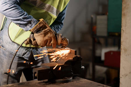 Hand of man work wearing gloves while Grinding metal and orange flying sparks in the factory Stockfoto