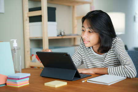 Asian girl is studying online via the internet on tablet digital while sitting at the table at night. Concept of online learning at home