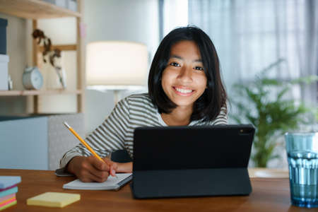 Homeschooling Asian girl doing homework And study online with tablet at the desk night. Portrait of Asia child happiness and smiling confidence looking to camera Standard-Bild