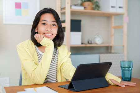 Portrait of Asian girl is studying online via the internet on tablet, Asia child happiness and smile confidently looking to camera while sitting on the table at night,  Concept of online learning at home