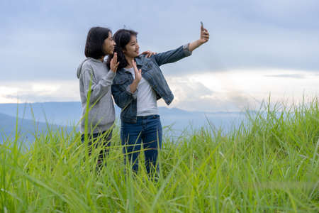 Tourist. group teen Asian woman social media taking photo selfie and vlogger live streaming video online at Phu Pa PO or Fuji Loei of Thailand