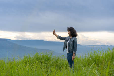 Happy Asian traveler teenage taking a photo with  mobile phone amidst nature beautiful