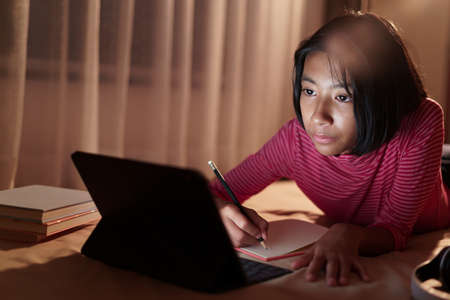 Asian girl is studying online via the internet on tablet while lying on the bed and doing homework in the night. Concept of online learning at home