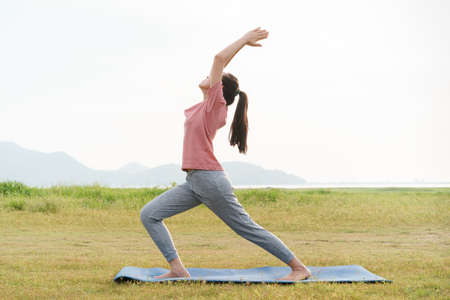 Asian young woman exercise practice warrior pose while on yoga mat at grass field outdoor