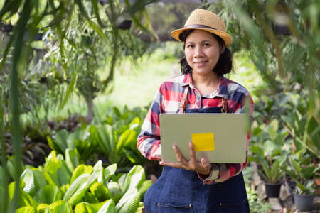 Portrait of Asian woman  happy and smiling while standing holding laptop in the Ornamental plant shop outdoor and looking to camera, Small business concept