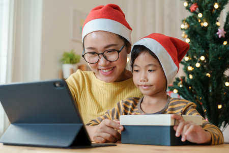 Christmas. Asian family with a mother and daughter giving gift box via video call together with tablet at home
