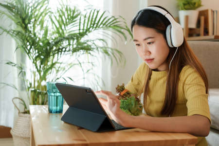 beautiful Asian young woman using a tablet and eat salad for lunch on table work at home. concept working from home Standard-Bild