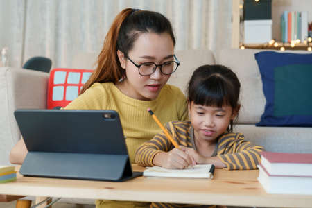 Asian family with a daughter do homework by using tablet with mother help. Happy smile Asia kid while sitting in the living room at home night, Concept of online learning at home