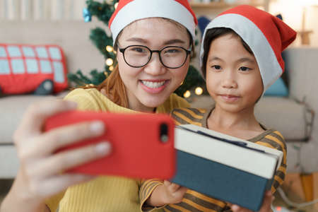 Asian family with a mother and daughter giving gift box via video call together with smartphone in the living room at home