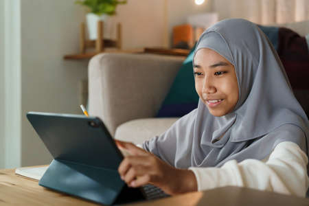 Muslim girl doing homework and using tablet with tutor via the internet on a table at night.