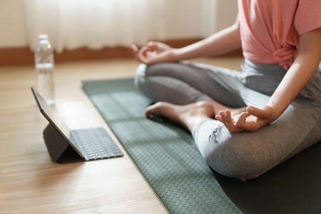 Close up of hand woman doing lotus yoga exercises on yoga mat with Training online on the tablet at home morning Stockfoto