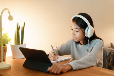 homeschooling, Asian girl doing homework and online learning with tutor on the tablet digital with headphones at home night Stock fotó