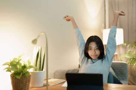Asian woman raise hand while learning online with tablet at home night Stock fotó