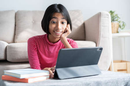 Asian girl expression excited on face while watching  tablet, Asia child emotion surprise at computer in the living room at home and sunlight
