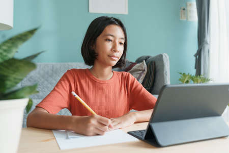 Asian girl is studying online via the internet on tablet and doing homework while sitting in the living room at home morning. Concept of online learning at home Stock fotó