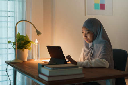 Muslim girl doing homework and using tablet with tutor via the internet on a table at night. Concept of online learning at home