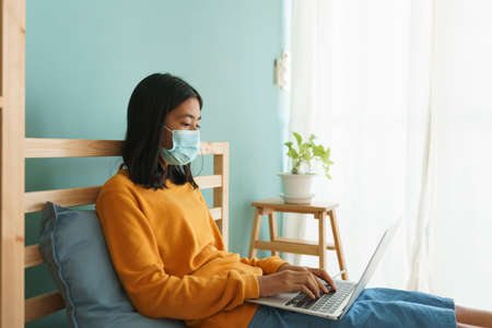 Asian woman wear medical mask while sitting  learning online with laptop computer at home, Concept online learning at home