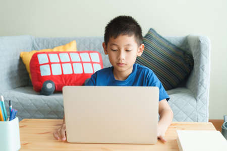 Asian boy learning online via internet with a tutor on laptop computer, Asia child is studying while sitting in the living room at home. Concept of online learning at home