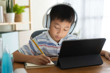 Asian boy learning online via internet with a tutor on a tablet digital with headphone, Asia child is studying while sitting in the living room at home. Concept of online learning at home Stock fotó