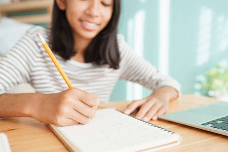 Hand of Asian girl doing homework and write on a notebook with a laptop computer, Concept of online learning at home