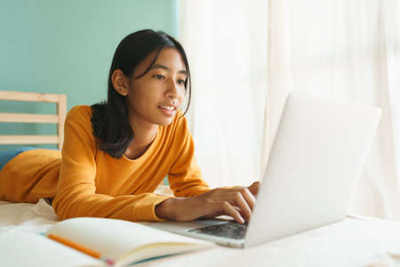 Asian woman learning online with a tutor via the internet with a laptop, Asia student girl video conference on a computer while lying on a bed in the morning, Concept online learning at home