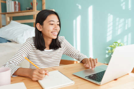 Asian girl learning online via the internet tutor on a laptop computer, Asia child is studying while sitting Interior at home morning. Concept of online learning at home Stock fotó
