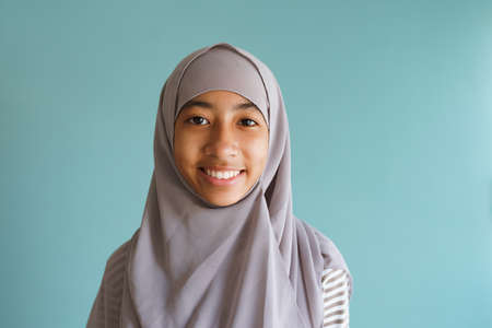 Happy Muslim little girl smile on the face, Asian woman wearing gray hijab while standing isolated on blue background. Portrait of women looking at camera confident